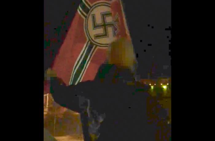 Aktivist från Soldiers of Odin ses hissa en hakkorsflagga.