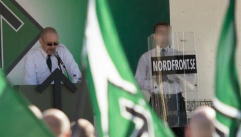 22-åringen (till höger) agerade sköldbärare när Nordiska motståndsrörelsen demonstrerade i Falun 1 maj förra året.